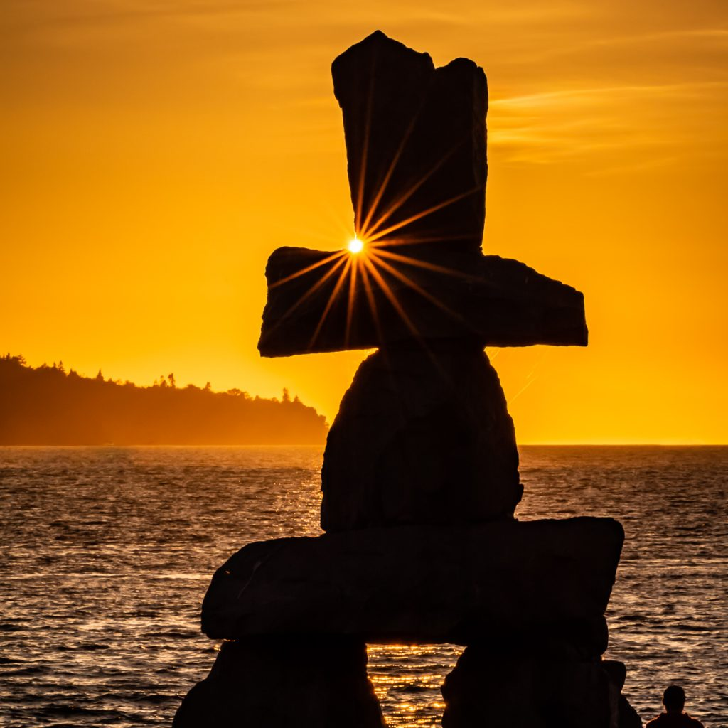 Inukshuk monument silhouetted against Vancouver sunset, with sunburst
